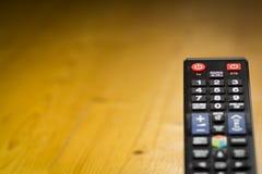 Telecontrole da televisão da tevê no foco de madeira da tabela sobre a tevê Imagem de Stock