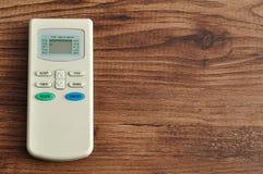 Telecontrole dos condicionadores de ar isolado em um fundo de madeira imagens de stock