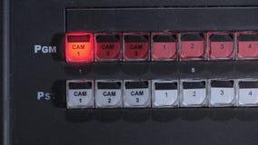 Teledirector sta inserendosi una macchina fotografica, spingente la chiave su un pannello di controllo nello studio della TV stock footage
