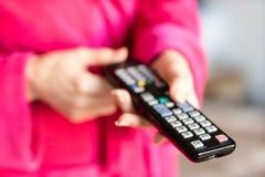 Teledirigido de la TV sostenido en el women& x27; manos de s Canales de la transferencia en t Foto de archivo libre de regalías