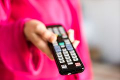 Teledirigido de la TV sostenido en el women& x27; manos de s Canales de la transferencia en t Imágenes de archivo libres de regalías