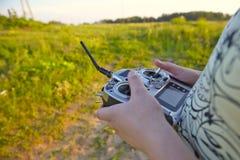Teledirigido para el quadrocopter, primer Transmisor para el dispositivo móvil que controla en las manos masculinas, naturaleza b Fotografía de archivo libre de regalías