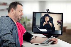 Teledoctor att kontrollera mans blodtryck arkivbild