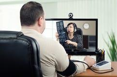 Teledoctor die hersenenröntgenstraal bekijken terwijl het meten van bloeddruk Stock Foto's