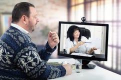 Teledoctor explica informe de la presión arterial al hombre Foto de archivo