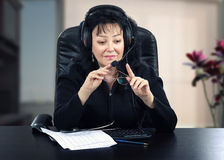Teledoctor in headset sits at black desk Stock Photo