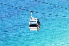 Teleférico na linha isolada no mar azul Cabo aéreo modular Foto de Stock Royalty Free