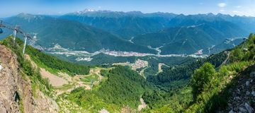 Teleférico na montanha Vista sobre as casas residenciais do vale verde, cercadas por montanhas altas nave fotos de stock royalty free