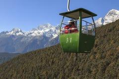 Teleférico no primeiro plano com alguns turistas internos e Jade Dragon Snow Mountain no primeiro plano Jade Dragon Snow Mountain Fotografia de Stock Royalty Free