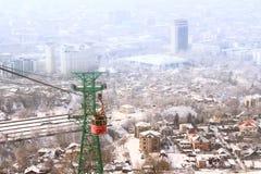 Teleférico vermelho com a vista de Almaty, Cazaquistão Fotografia de Stock