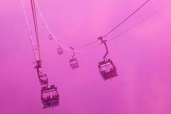 Teleféricos de la silueta en niebla Foto de archivo