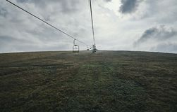 Teleferica fra i campi sulla collina fotografia stock