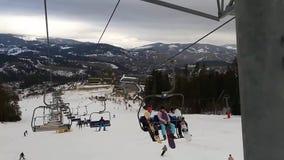 Teleferica in montagne per gli sciatori nella stazione sciistica seggiovia La gente scala l'ascensore alla stazione sciistica Sci video d archivio