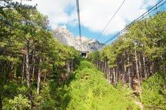 Teleferica nelle montagne sopra la foresta Fotografia Stock