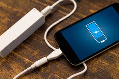 Telefon ładuje z energetycznym bankiem. fotografia royalty free