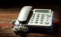 Telefon auf hölzernem Hintergrund Lizenzfreie Stockfotografie