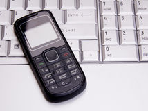 Telefon auf Laptoptastatur Stockbilder