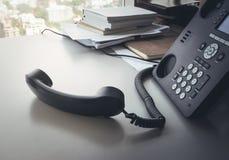 Telefon auf Schreibtisch im Büro lizenzfreie stockbilder