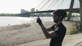 Telefon för cyklistinnehavkamera som tar bilder av flod- och stadsanseendet på kullen Bro- och solsken i bakgrund L?ngsam kvickhe arkivfilmer