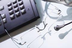 Telefon för exponeringsglas för hörlurar med mikrofon för tabell för arbetsplatskontorsskrivbord arkivbilder
