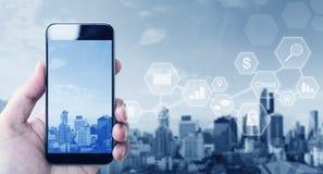 Telefon för hållande mobil för hand smart, på stadsbakgrund med applikationsymboler royaltyfri bild