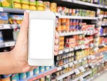Telefon för hållande mobil för hand smart på supermarketsuddighetsbakgrund arkivbild