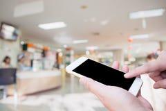 Telefon för hållande mobil för kvinnahand smart med sjukhusbakgrund arkivfoton