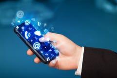 Telefon för innehav för affärsman smart med massmediasymboler Royaltyfria Bilder