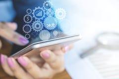 Telefon för innehav för hand för affärskvinna smart med teknologikugghjulet Royaltyfri Fotografi
