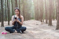 Telefon för lycklig för ung kvinna för sport sund användande smart för flicka övning för livsstil efter hantelgenomkörare royaltyfri fotografi