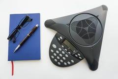 Telefon för Voip IP-konferens med anteckningsboken och glasögon för att ta minut av mötet i regeringsställning Arkivfoto
