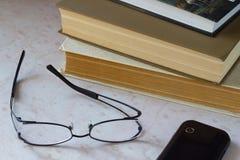 telefon Gläser und alte Bücher auf dem Desktop Stockfotografie