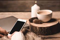 Telefon i händerna av flickan, en vit kopp med kaffe, stearinljuset och kottar arkivfoton