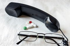 Telefon i kolorowe pigułki na lekkim tle okulary obraz royalty free