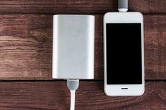 Telefon i powerbank na drewnianych biurkach Zdjęcie Stock