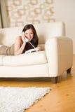 Am Telefon: junge Frau, die im Aufenthaltsraum benennt lizenzfreie stockbilder