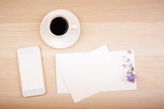 Telefon, kaffe och tomma kort Arkivbild