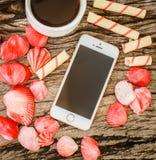 Telefon, kawa, ciastka i skorupy na drewnianej desce, fotografia royalty free