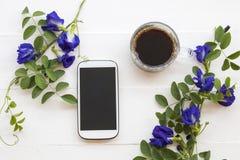 Telefon komórkowy, Czarna kawa z kwiatu motyliego grochu lokalną florą Asia obraz royalty free