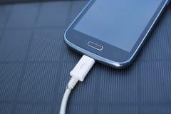 Telefon komórkowy ładuje z energią słoneczną - ładowarka Fotografia Royalty Free