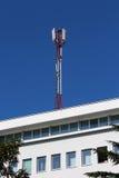 Telefon komórkowy anteny wierza na górze białego budynku biurowego fotografia royalty free