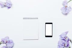 Telefon komórkowy, błękitów kwiaty i notepad lying on the beach na białym backgr, Obraz Stock