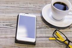 telefon komórkowy, filiżanka kawy, szkła Fotografia Stock
