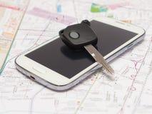 Telefon komórkowy i klucza samochód na mapie. Obrazy Royalty Free