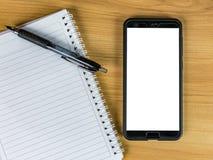 Telefon komórkowy i notatnik z piórem na lekkiej drewno stołu kopii przestrzeni obraz stock