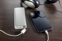 Telefon komórkowy i władza deponujemy pieniądze baterię na ciemnym tle Obrazy Stock