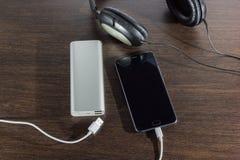 Telefon komórkowy i władza deponujemy pieniądze baterię na ciemnym tle Fotografia Royalty Free