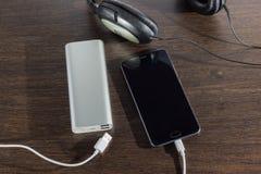 Telefon komórkowy i władza deponujemy pieniądze baterię na ciemnym tle Obraz Royalty Free