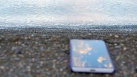 Telefon komórkowy jest o otoczak plaży ocean Spokój macha bicie przeciw brzeg Pojęcie zbiory