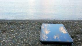 Telefon komórkowy jest o otoczak plaży ocean Spokój macha bicie przeciw brzeg Pojęcie zdjęcie wideo